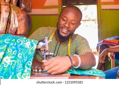 young african man who is a tailor smiling while working on a piece of ankara material