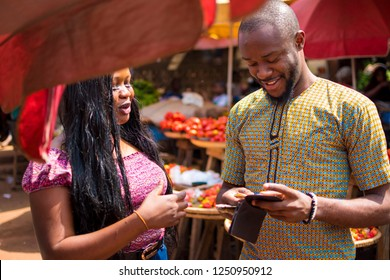 young african man and woman in a local african market. young african man bringing out money from his wallet to give to a woman in a local african market