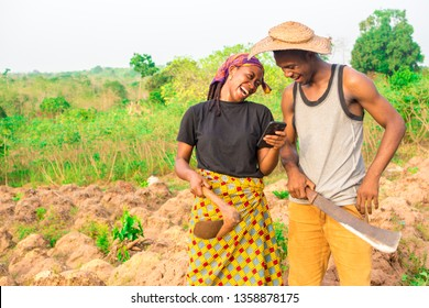 young african man and woman on a farm laughing while viewing something on a mobile phone. young african farmers laughing while checking something on a smartphone