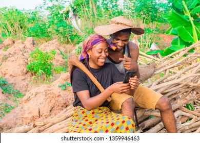 young African man and woman on a farm sitting together on a pile of wood smiling while viewing content on a mobile phone
