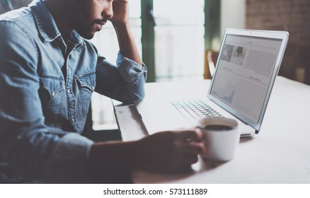 Young African man working on laptop while spending time at home.Concept of coworking people using mobile devices.Blurred information background screen.Selective focus