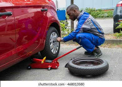 Young African Mechanic Changing Tire Of A Red Car With Wrench