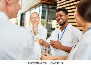 Young african medicine student welcomes senior doctor with handshake in coffee break