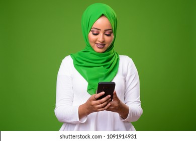 Young African Muslim woman against chroma key with green background