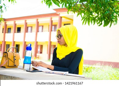 Young African Muslim writer, writing her new book for publication. student doing her course work
