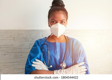 A young African nurse wears a blue uniform, a mask and gloves while standing with her arms crossed in the hospital.