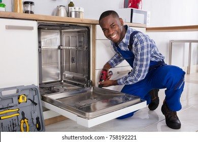 Young African Repairman Fixing Dishwasher In Kitchen