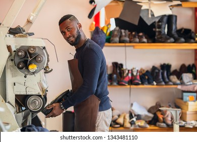 Young african shoemaker performs shoes in the studio craft grinder machine.