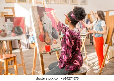 Young african student painting still life painting at the studio