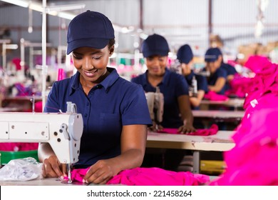 young african textile worker sewing on production line