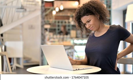 Young African Woman with Back Pain using Laptop in Cafe