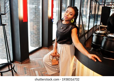 Young african woman in black blouse at cafe.