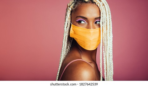 Young african woman with blonde box braids wearing protective face mask. Female with african hair style and face mask looking away on pink background.