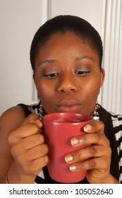 Young african woman blowing on her hot coffee cup