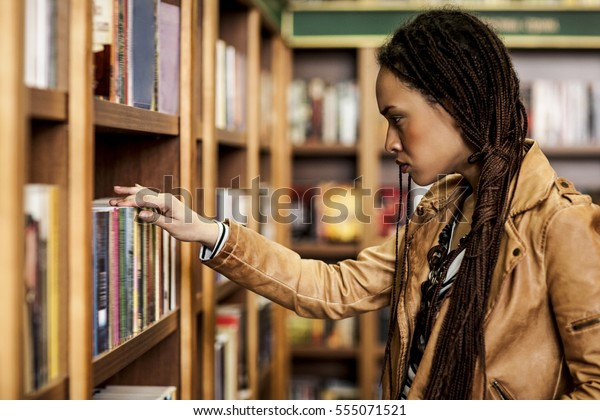 Young African woman buying books at a bookstore.