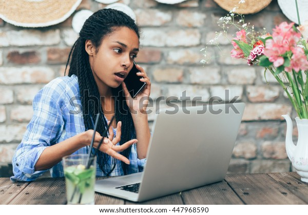 Young african woman at cafe working on laptop and talking on mobile phone