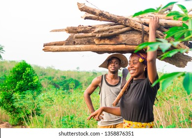 young african woman carrying a pile of wood on her head and a young black man working behind her onna farm
