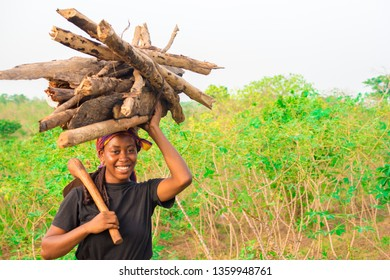 young African woman carrying a pile of wood on her head and a hoe from the farm