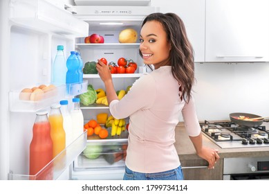 Young african woman choosing products in fridge in kitchen. Healthy food concept.