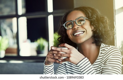 Young African woman drinking a fresh cup of coffee and smiling while sitting alone at a table in a cafe