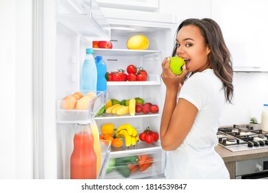 Young african woman eating apple near open fridge in kitchen. Healthy food concept.