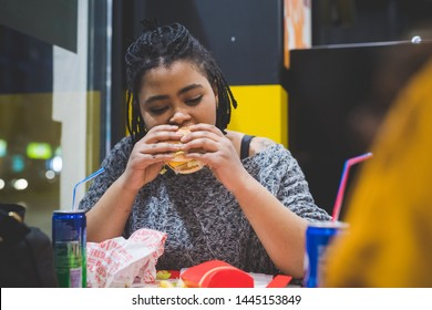 young african woman eating in fast food – appetite, break, relax