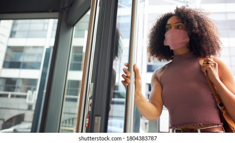 Young African woman entering office wearing face mask looking off camera
