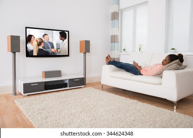 Young African Woman Falling Asleep While Watching Television At Home