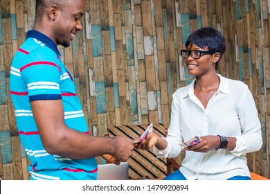 a young african woman giving a man some money