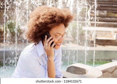 Young African Woman With Glasses Using Smartphone. Outdoor Portrait Of Mixed Race Student, Casual Wear , Looking At The Down