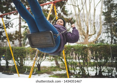 young african woman having fun on the swing outdoor in winter day – movement, joyful, youth culture