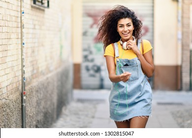 Young African woman with headphones and black curly hairstyle walking outdoors. Happy girl wearing yellow t-shirt and denim dress in urban background.