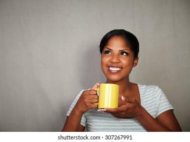 Young african woman in her 20s holding a tea cup while standing against grey background