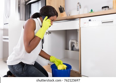 Young African Woman Holding Yellow Napkin Calling Plumber With Mobile Phone