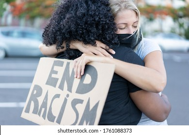 Young african woman hugging a white northern woman after a protest - Northern woman with end racism bannner in her hands - Concept of no racism