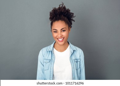 Young african woman isolated on grey wall studio casual daily lifestyle smiling