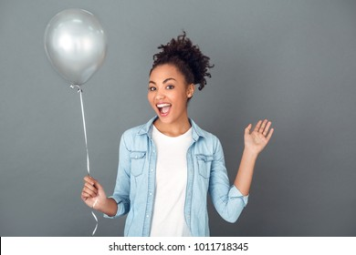 Young african woman isolated on grey wall studio casual daily lifestyle birthday balloon