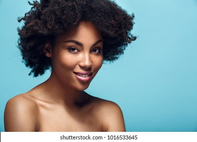 Young african woman isolated on blue wall studio fashion photoshoot smiling