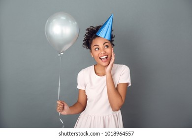 Young african woman isolated on grey wall studio celebration concept holding balloon cheerful