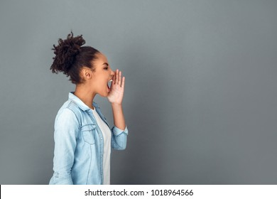 Young african woman isolated on grey wall studio casual daily lifestyle screaming