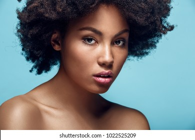Young african woman isolated on blue wall studio fashion photoshoot confident