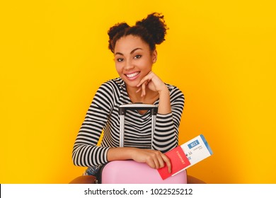 Young african woman isolated on yellow wall studio teen style traveler sitting on suitcase