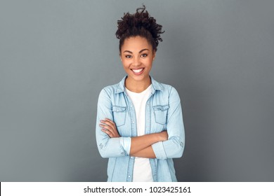 Young african woman isolated on grey wall studio casual daily lifestyle crossed arms