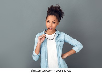 Young african woman isolated on grey wall studio casual daily lifestyle student biting glasses