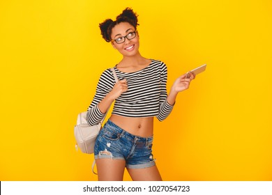 Young african woman isolated on yellow wall studio teen style with knapsack and smartphone