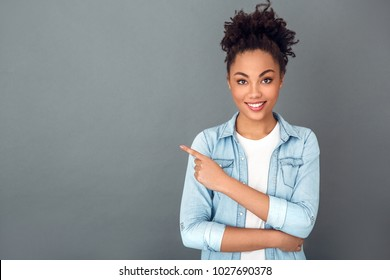Young african woman isolated on grey wall studio casual daily lifestyle copyspace