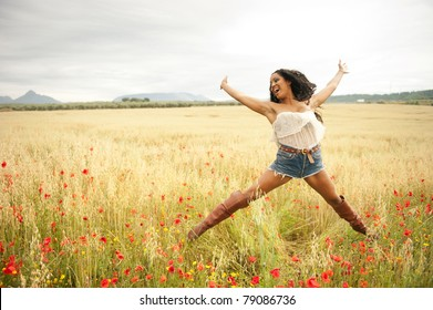 Young african woman jumping in field
