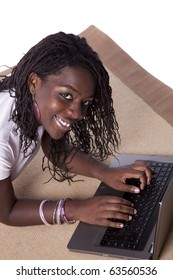 young african woman laying down on the carpet surfing the internet
