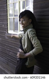 A young African woman leans against an old wood slatted house smiling with splendor