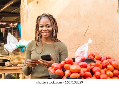 young african woman in a local african market using her mobile phone and credit card